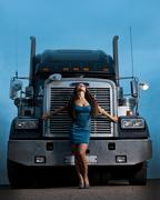 young pretty girl posing before huge cargo truck - stock photo