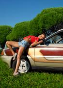 Pretty woman pin-up style lay on retro car Stock Photos