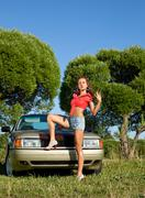 pin-up style young woman stay before retro car - stock photo
