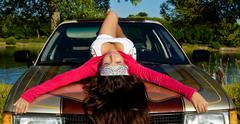 beauty young girl lay on car at summer sunset - stock photo