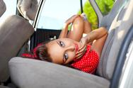 Stock Photo of young sexy woman lay in car - pinup style