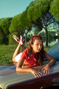 young woman lay on retro car in summer sunset - stock photo