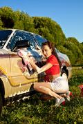attractive pinup girl washing a car at summer - stock photo