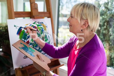 Stock photo of happy elderly woman painting for fun at home