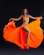 beauty dancer posing in orange veil - arabia style - stock photo