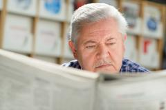 elderly man with mustache reading paper in library - stock photo