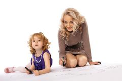 Happy mother look at daughter draw and smile Stock Photos