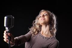 Beautiful blond woman portrait sing in microphone Stock Photos