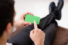 Stock Photo of businessman using smartphone with green screen for web and e-mail