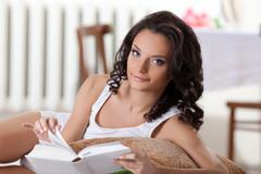Stock Photo of cute woman read book in morning interior