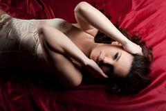 Young naked girl lay on red - close breast hands Stock Photos