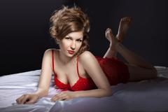 Sexy woman in red posing on white silk bed Stock Photos