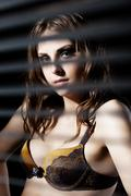 cute woman in bra hide behind venetian blind - stock photo