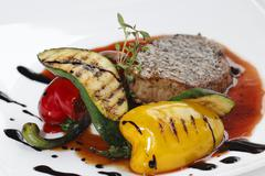 roasted piece of meat with vegetables - stock photo