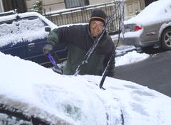 Man scraping snow from windshield Stock Photos
