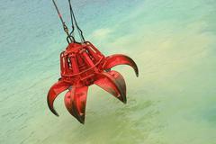 Bucket of crane above the water - stock photo
