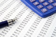 Studying financial numbers on a printed spreadsheet. Stock Photos