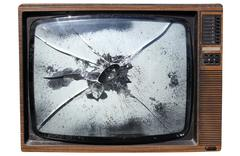 an old trashed tv with a smashed screen. - stock photo