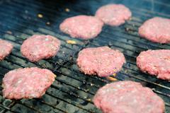 raw hamburgers on the grill - stock photo