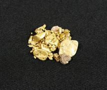 Gold nuggets on black Stock Photos