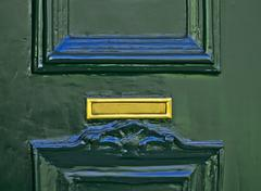 Golden Mail Slot on Green Door - stock photo