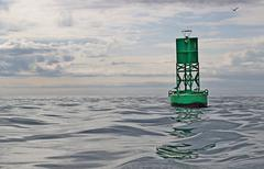navigational buoy in calm seas with clouds - stock photo