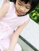 Pink dress girl on bench Stock Photos