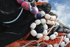 Pile of commercial fishing nets with blue sky Stock Photos