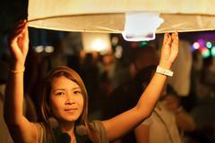woman launching fire lantern - stock photo