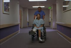 Tracking shot of caucasian male nures as he pushes a caucasian female patient in Stock Footage