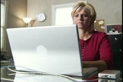 medium shot of a blonde woman at her desk as her daughter comes in to show her - stock footage
