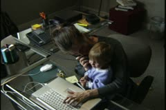 High angle medium shot of a woman in her home office with a child on her lap as Stock Footage