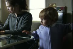 Medium shot of a woman looking after her young child as she works in her home Stock Footage