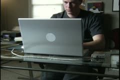 Medium shot of a young man as he sits and types on the computer in his home Stock Footage