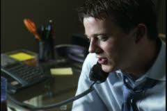 Close up shot of a young man as he uses the phone and his computer in his home Stock Footage