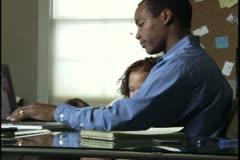 Medium shot of a man working in his home office while his young daughter sleeps Stock Footage