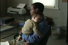 Medium shot of a man holding his young baby as he works on his computer in his Stock Footage