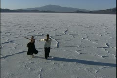 high angle wide shot of two young people dancing playfully together in a desert - stock footage
