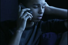Close up shot of a teenage male at night as he talks on a cell phone Stock Footage