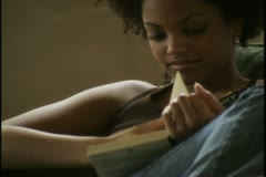 Medium close up of a young woman as she sits and reads a book Stock Footage