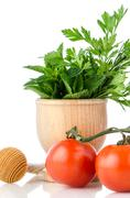 tomatoes and green herb leafs - stock photo