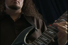 close up on an electirc guitar as a young man plays wildly - stock footage