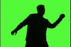 Medium shot up of a man as he dances playfully silhouetted against green Stock Footage