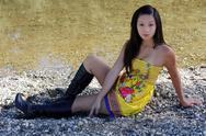 Stock Photo of young asian american woman yellow dress river