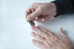 Older man trims fingernails.jpg Stock Photos