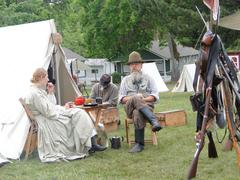 a sutler and his wife relax by their tent in the confederate camp - stock photo