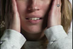 Close up video portrait of a sick young woman as she holds her head in pain Stock Footage