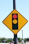 traffic signal ahead sign against blue sky with autos - stock photo