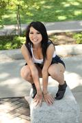 Young asian american woman squatting on granite block Stock Photos