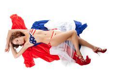 Smiling young woman in bikini lay on fabric Stock Photos